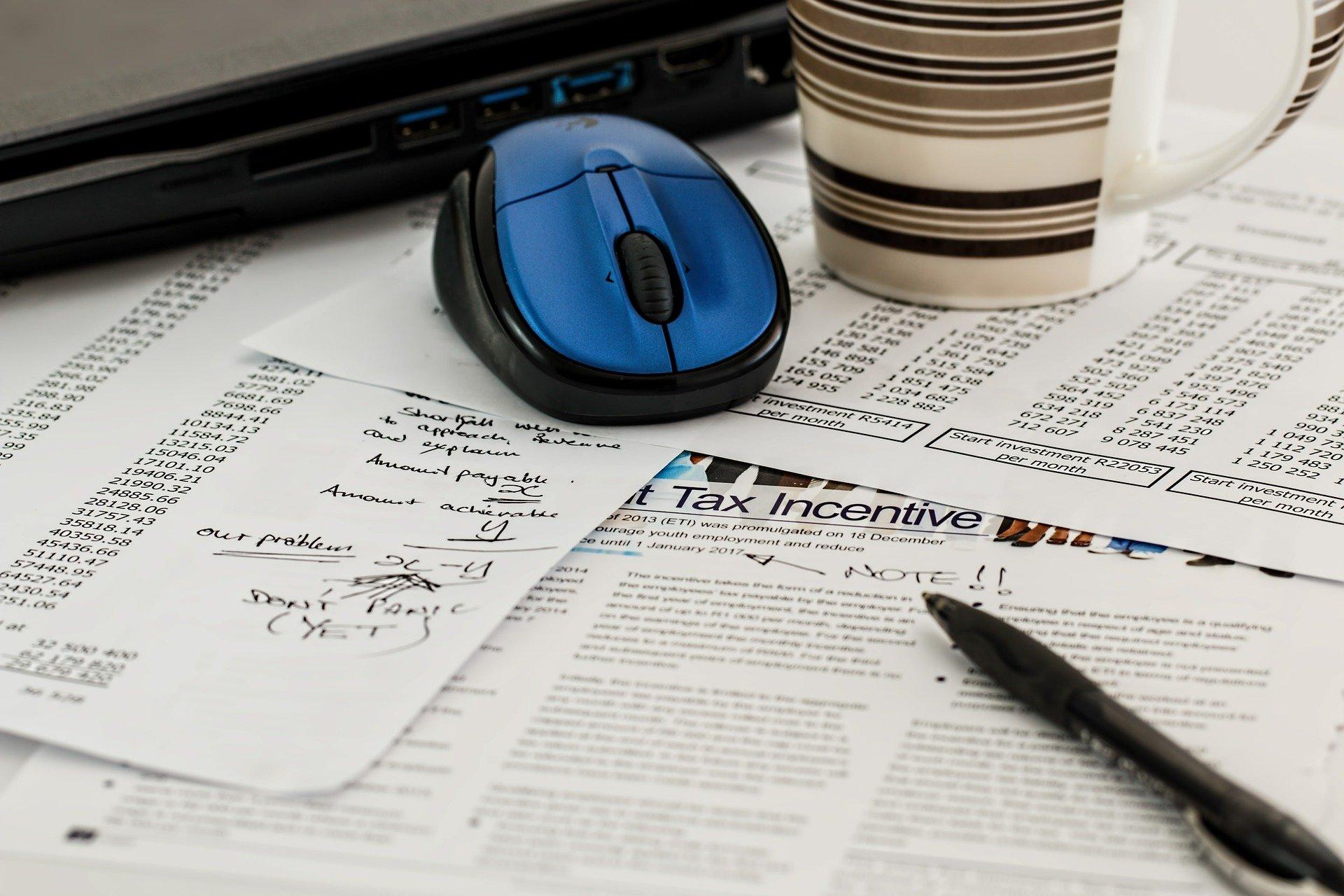 Tax forms sit on a desk under a pen.